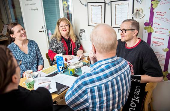 Kajastuksessa vaalitaan puhumisen kulttuuria. Pöydän ääressä ajatuksia vaihtaa moniammatillinen joukko: asumisyksikön esimies Outi Priia, sosiaalipalvelujen johtaja Merja Paavola, sairaanhoitaja Santtu Koivula ja työsuojeluvaltuutettu Tero Järvimäki sekä pöydän päässä työhyvinvointipäällikkö Katri Mannermaa.