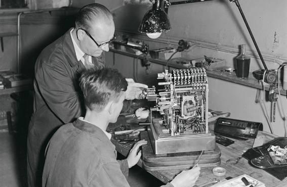 Oppipoika saa opastusta vanhemmalta työntekijältä. Osuustukkukaupan korjaamolla Helsingissä asetettiin kassakoneen kuitti- ja värinauhamekanismia paikoilleen vuonna 1955.