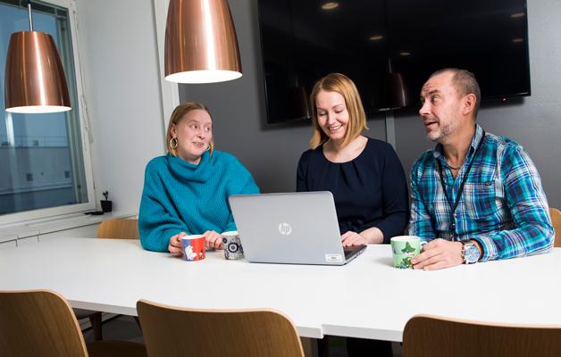 Tilda Lindgren, Mari Kauranen och Anssi Roivainen trivs i det gemensamma kafferummet på arbetsplatsen.