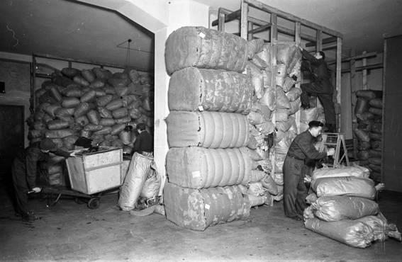Keru Oy:n varastossa Helsingissä työskenneltiin lumppupinojen keskellä vuonna 1945. Nykyisiä työturvallisuussäädöksiä varasto ei täyttäisi.