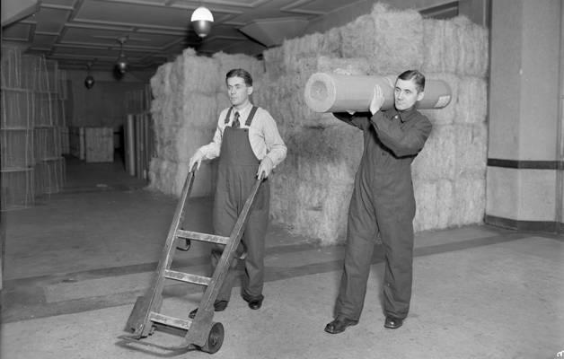 OTK:n pukutehtaan mainoskuva vuodelta 1943 esitteli käytännöllisiä työhaalareita varastotyöhön.