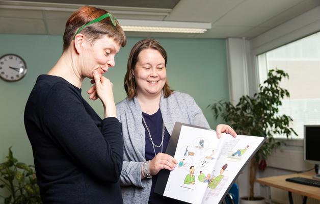 Sari Kivimäki ja Johanna Eskelinen selaavat kuvakommunikaatiokansiota. Kuvakommunikaatiota käytetään muun muassa työn ohjeistukseen ja perehdyttämiseen.
