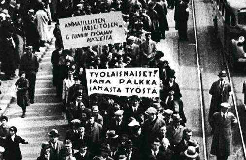 Yleislakkokulkue Helsingissä vuonna 1956. Yleislakon päätavoitteena olivat palkankorotukset, mutta myös työviikon lyhentäminen oli esillä. Banderollien vaatimus 36-tuntisesta työviikosta oli edellä aikaansa.